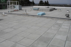Flat roof construction using paving pads