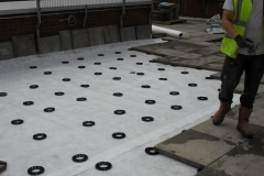 Plastic pave pads supporting paving slabs