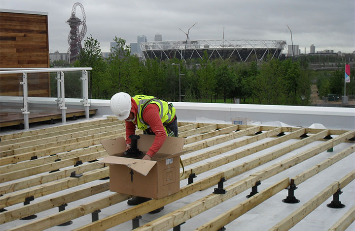 A worker installing decking over pedestals with the Olympic stadium in the background