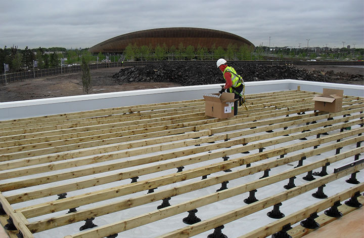 A worker installing decking over pedestals with the Olympic stadium