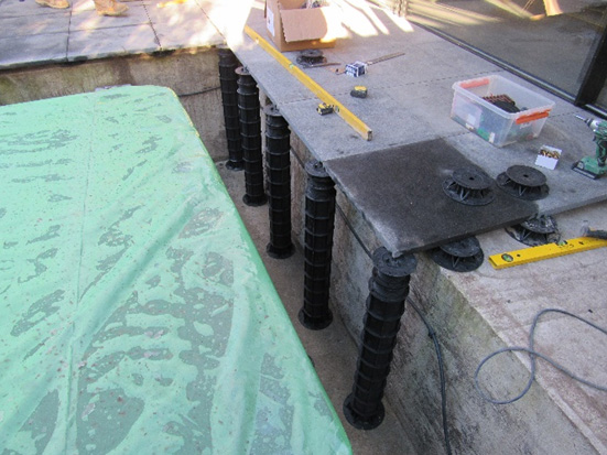 An image of adjustable support pedestals being installed