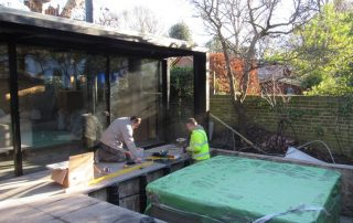 An image of adjustable support pedestals being installed at Grove Park, Chiswick