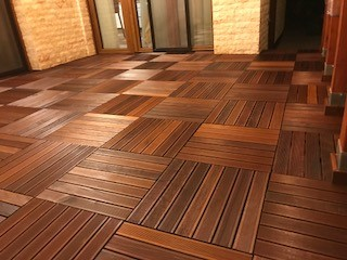 An image of an installation of hardwood decking tiles