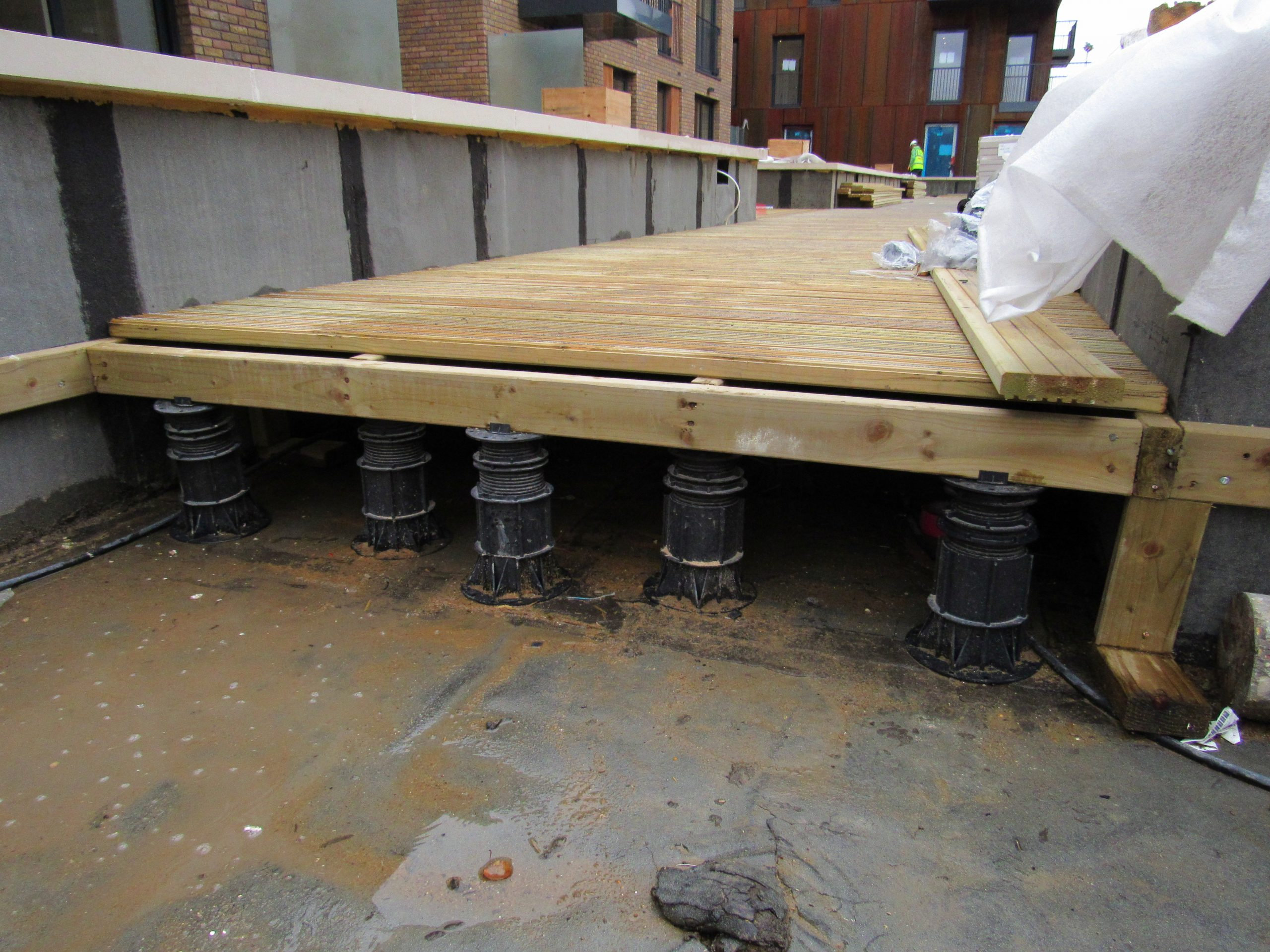 Adjustable decking pedestals joists and deck boards